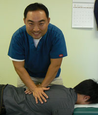 Spinal adjustment being performed by Dr. Kim